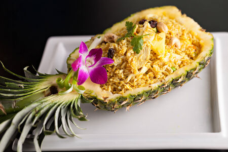 Freshly prepared pineapple fried rice served inside of a pineapple carved like a bowl. photo