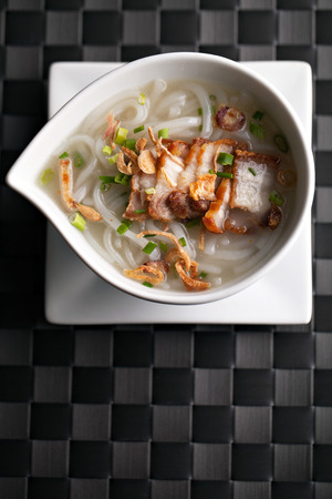 Closeup top down view of Thai style crispy pork rice noodle soup in a bowl with copy space. photo