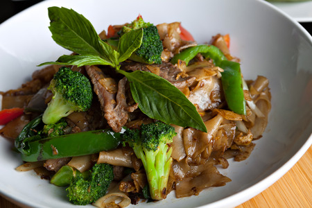 beef curry: Pad kee mao drunken noodle thai dish closeup with beef and mixed vegetables.