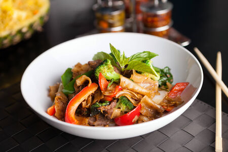 Pad kee mao drunken noodle thai disk with beef and mixed vegetables. Imagens