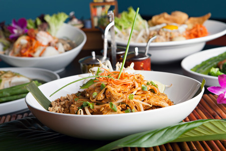 Chicken pad Thai with a variety of other fine Thai food dishes.  Shallow depth of field. photo