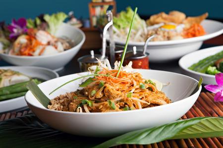Kip pad Thai met een verscheidenheid aan andere heerlijke Thaise gerechten worden geserveerd. Ondiepe diepte van het veld.