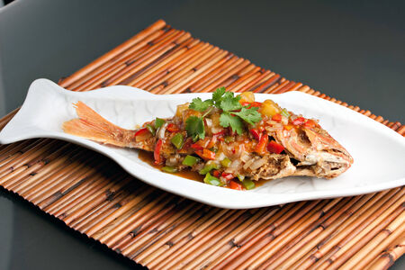 Freshly prepared Thai style whole fish red snapper dinner with tamarind sauce on a white fish shaped plate.