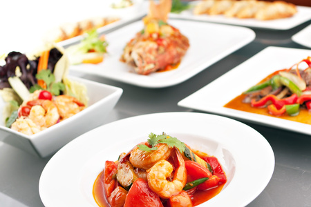 culinary arts: Variety of Thai style whole fish red snapper sweet and sour shrimp gyoza dumplings sesame breads seafood salad and other spicy Thai dishes. Stock Photo