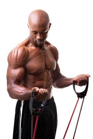 Ripped body builder working out his biceps using a resistance band.  photo