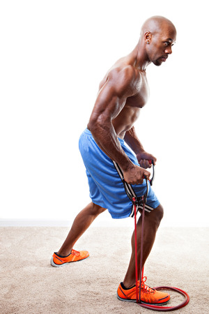 Ripped body builder working out  using a resistance band.  photo