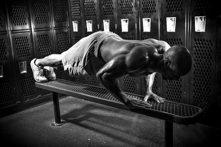 Portrait of a lean toned and ripped muscle fitness man under dramatic low key lighting in black and white. photo