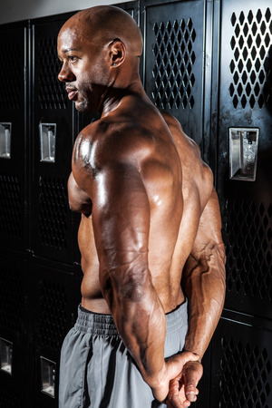 Portrait of a muscle fitness mans back and shoulders in the locker room. photo