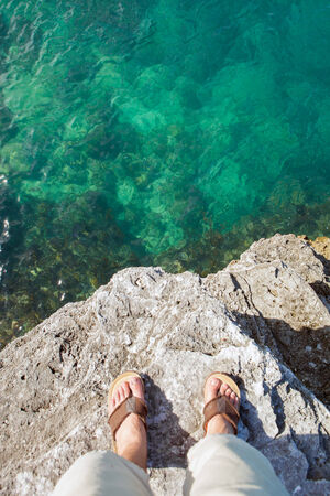 cliff edge: Self portrait showing a mans feet standing on the edge of a cliff by the tropical ocean waters in Bermuda.