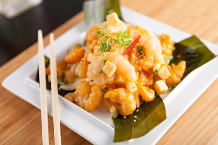 plating: Thai crispy shrimp dish with apple and sesame seeds presented beautifully on a white square plate with chopsticks.