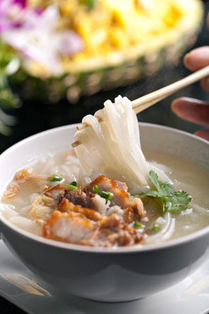 thai noodle soup: Closeup of a person eating Thai style crispy pork rice noodle soup from a bowl with chopsticks. Pineapple fried rice in the background.