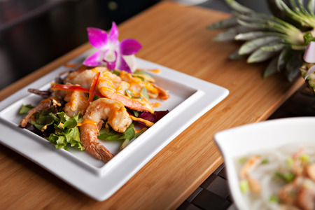 plating: Thai shrimp dish presented on a white square dish.  Shallow depth of field. Stock Photo