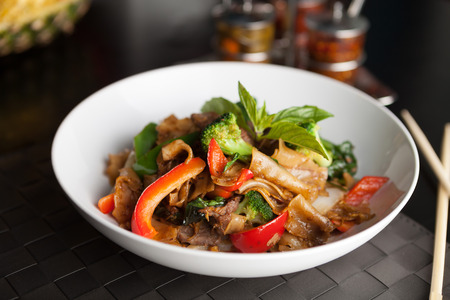 stir fried: Pad kee mao drunken noodle thai dish with beef and mixed vegetables.