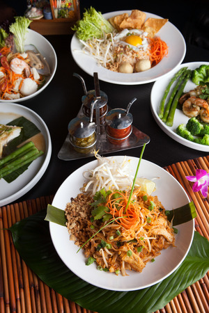 Chicken pad Thai with a variety of other fine Thai food dishes.  Shallow depth of field.