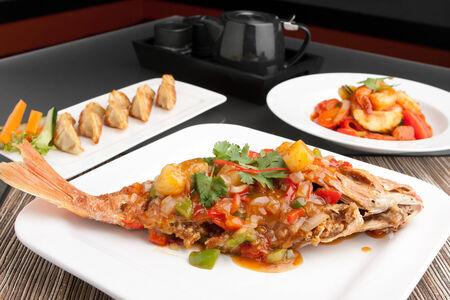pescado frito: Recién preparada al estilo tailandés toda cena de pescado pargo rojo con camarones agridulce y pan frito aperitivo gyoza bolas de masa hervida.