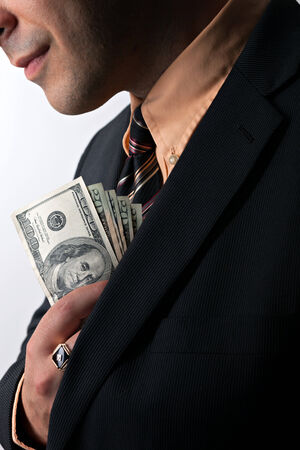 Close up of a business mans hand hiding money in his suit jacket pocket. photo