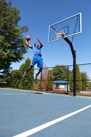 Young basketball player drives to the hoop with some fancy moves. photo
