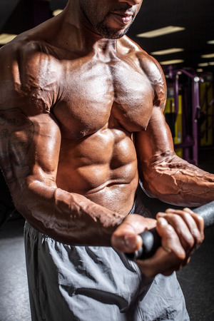 out of body: Muscular body builder working out  at the gym.