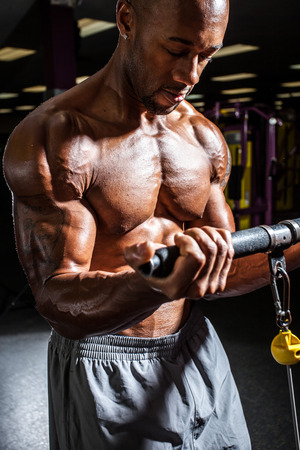 Fit male body builder working out  using a resistance weight machine. photo