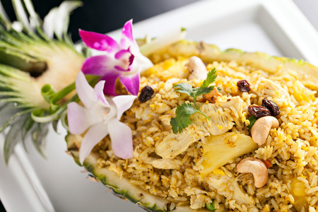 Freshly prepared pineapple fried rice served inside of a pineapple carved like a bowl.