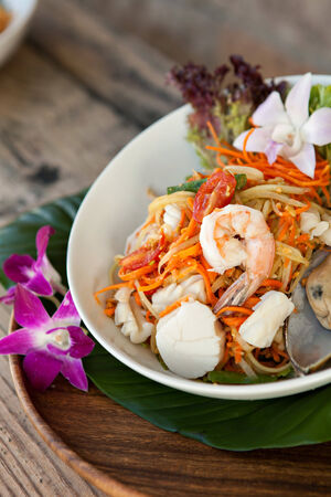 Traditional dish of freshly prepared Thai food.  Thai seafood and som tum green papaya salad. photo
