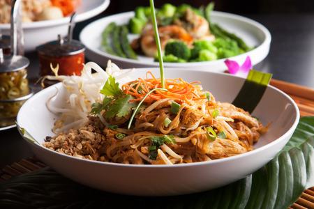 Kip pad Thai met een verscheidenheid aan andere fijne Thaise gerechten worden geserveerd. Ondiepe diepte van het veld.