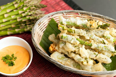 battered: Thai style appetizer of fried tempura asparagus with dipping sauce.  Stock Photo