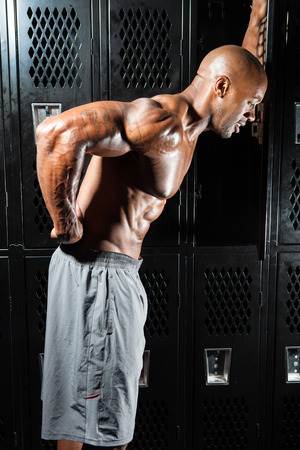 Portrait of a muscle fitness man reaching for his lower back in pain photo