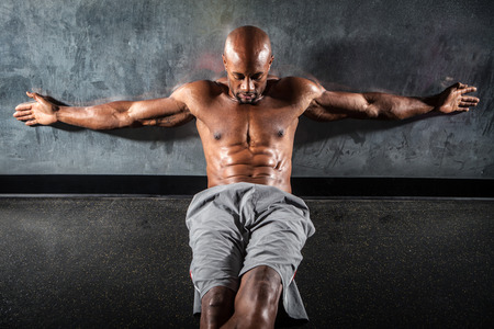 jacked: Portrait of a lean toned and ripped muscle fitness man under dramatic low key lighting.
