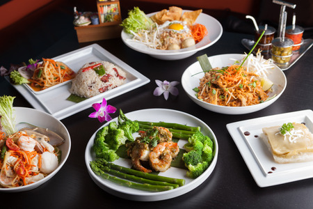 Shrimp scampi seafood dish with broccoli and asparagus and a variety of other Thai food dishes. Stock Photo