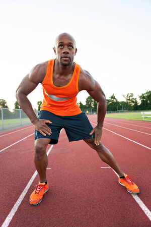 African American man in his 30s stretching at a sports track outdoors. photo