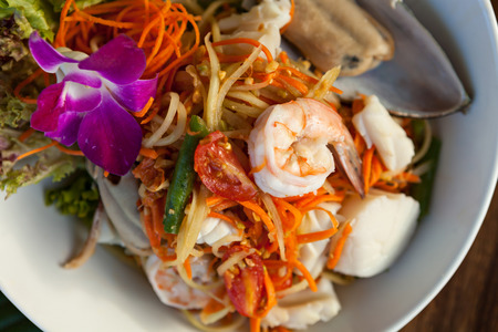 Traditional dish of freshly prepared Thai food.  Thai seafood and som tum green papaya salad. photo