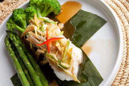 Freshly prepared Thai style sea bass fish dinner with asparagus and appetizer with a contemporary presentation. photo