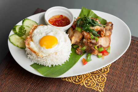 atop: Traditional Thai dish crispy pork with a fried egg atop the jasmine rice served with chili sauce. Stock Photo