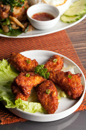 Thai style spicy chicken wings on a round white plate. photo