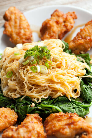 Thai style fried chicken wings on a round white plate with egg noodles and spinach. photo