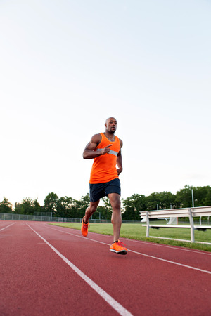 African American man in his 30s running at a sports track outdoors.