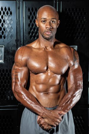 Portrait of a lean toned and ripped muscle fitness man under dramatic low key lighting in the locker room. photo