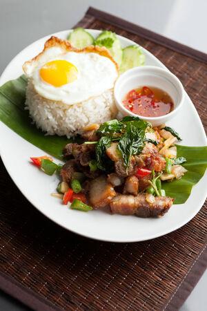 santa cena: Plato de cocina tailandesa tradicional cerdo crujientes con un huevo frito encima del arroz jazm�n servido con salsa de chile. Foto de archivo