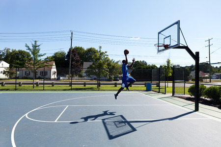 Young basketball player driving to the hoop for a high flying slam dunk. photo