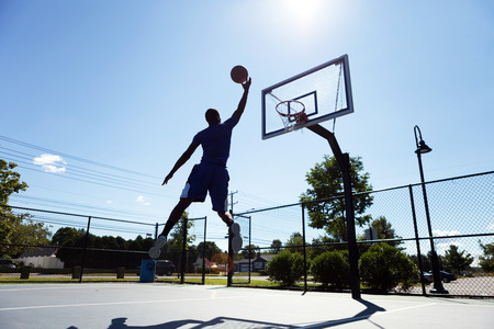 A young basketball player going up for a layup.  Intentionally back lit with bright lens flare. photo