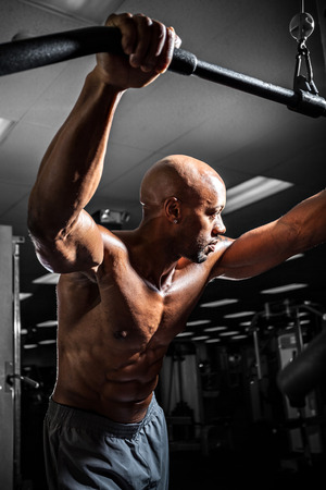 weight machine: Fit male body builder working out  using a resistance cable weight machine.