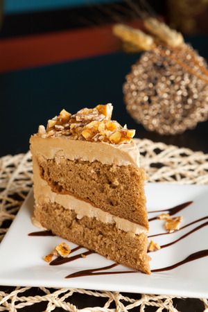 Slice of almond toffee cake with coffee flavored icing.