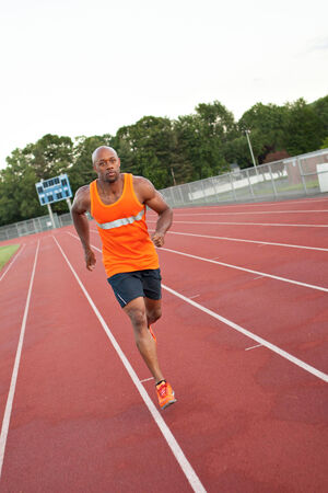 of african descent: African American man in his 30s running at a sports track outdoors.
