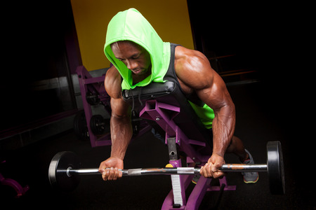 lifter: Toned and ripped lean muscle fitness man lifting weights on a curling bar. Stock Photo