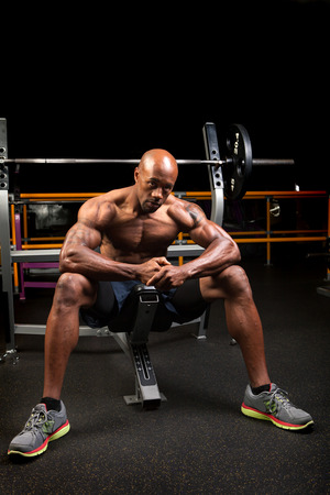 six packs: Weight lifter sitting at the bench press about to lift a barbell.