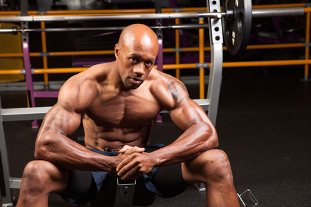 6 pack: Weight lifter sitting at the bench press about to lift a barbell.