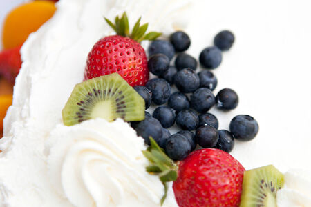 White frosted cake covered with fresh fruit toppings. Shallow depth of field.