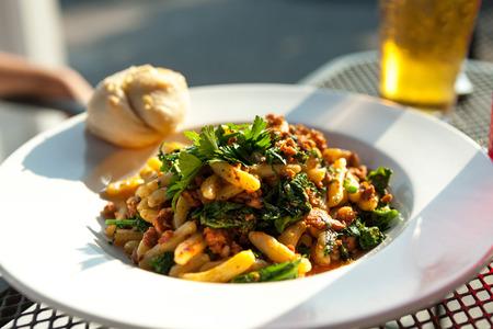 Knoflookolie Rabe gerecht met worst dan penne pasta gepresenteerd in een witte schotel. Stockfoto
