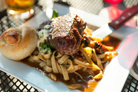 Petite filet mignon on a bed of homemage pasta with mushrooms and truffle oil.  Shallow depth of field.